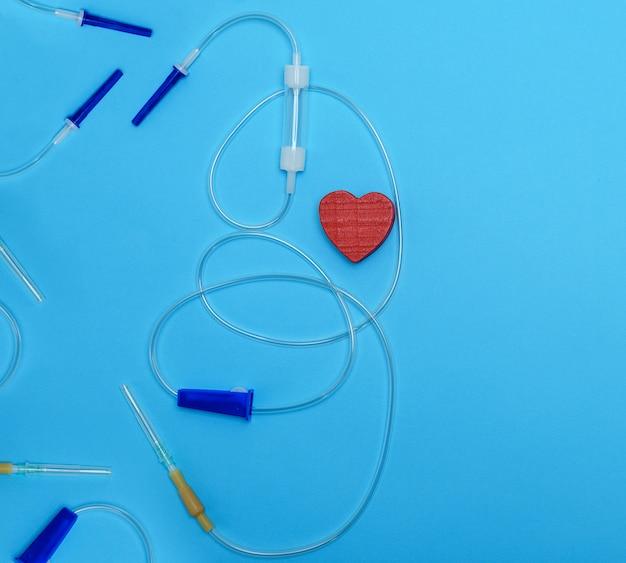 Conta-gotas de plástico vazia com agulhas e coração vermelho no fundo azul