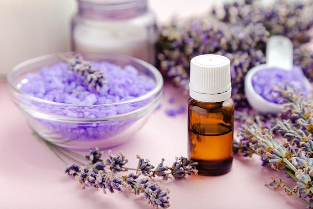 Conta-gotas de vidro de óleo essencial de lavanda com produto de banho sal marinho violeta sobre fundo de cor rosa. flores frescas de lavanda. tratamento de aromaterapia. cosméticos de spa para cuidados da pele, erva boticária de lavanda