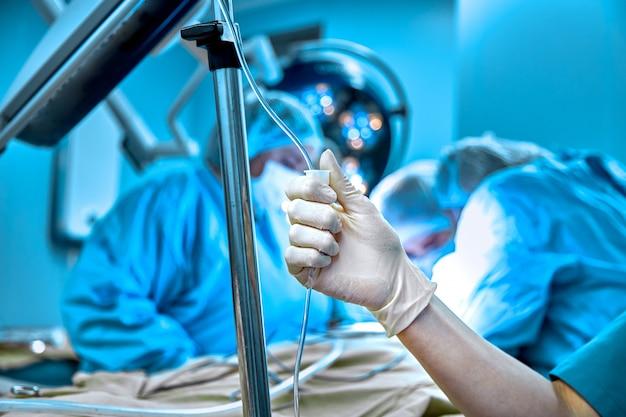 Conta-gotas em um close de veia em um fundo cirúrgico operacional. medique a mulher em luvas estéreis, preparando um paciente para a cirurgia.