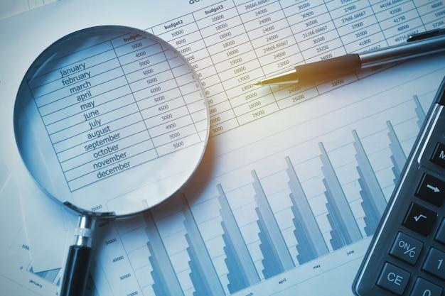 Contabilidade dos documentos de negócio com calculadora, pena e lupa.