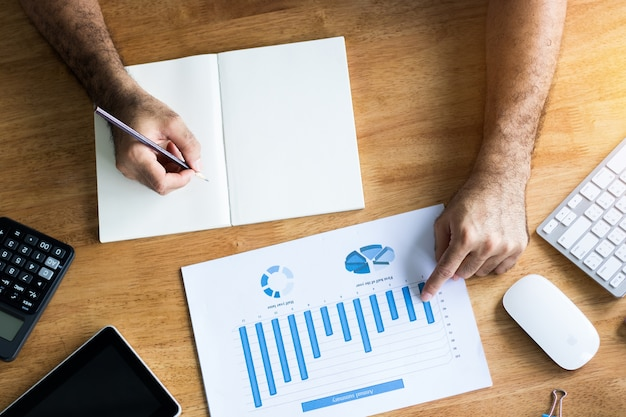 Contabilidade, e, gerente, escrita, papel, e, olhar, financie gráfico, ligado, madeira, escrivaninha