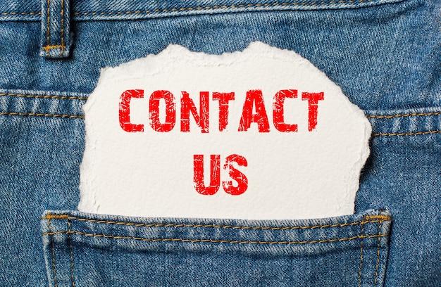 Contacte-nos em papel branco no bolso da calça jeans azul