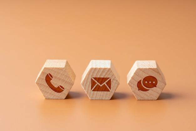 Contacte-nos ícone no quebra-cabeça de madeira com a mão
