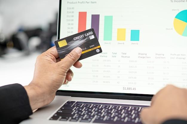 Contador asiático trabalhando, calculando e analisando a contabilidade do projeto de relatório com notebook e cartão de crédito no conceito moderno de escritório, finanças e negócios.