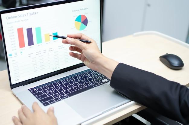 Contador asiático trabalhando com gráfico no laptop