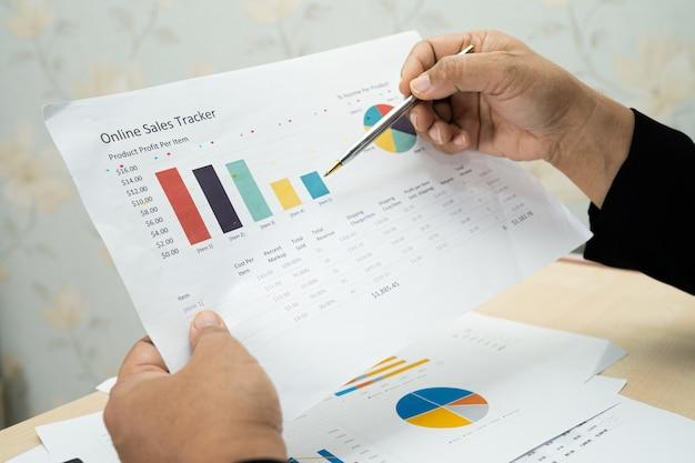 Contador asiático trabalhando com projeto de relatórios financeiros.