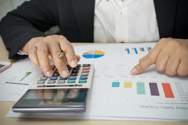 Contador asiático trabalhando e analisando contabilidade de projeto de relatórios financeiros com gráfico gráfico e calculadora no conceito moderno de escritório, finanças e negócios.