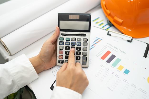 Contador asiático trabalhando e analisando projetos de relatórios financeiros.