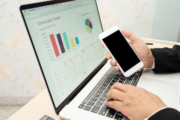 Contador asiático trabalhando e analisando relatórios financeiros, contabilidade de projetos com gráfico gráfico e calculadora