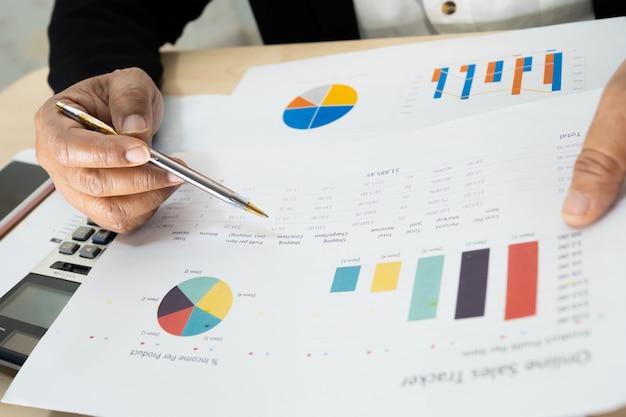 Contador asiático trabalhando projeto de relatórios financeiros com gráfico.