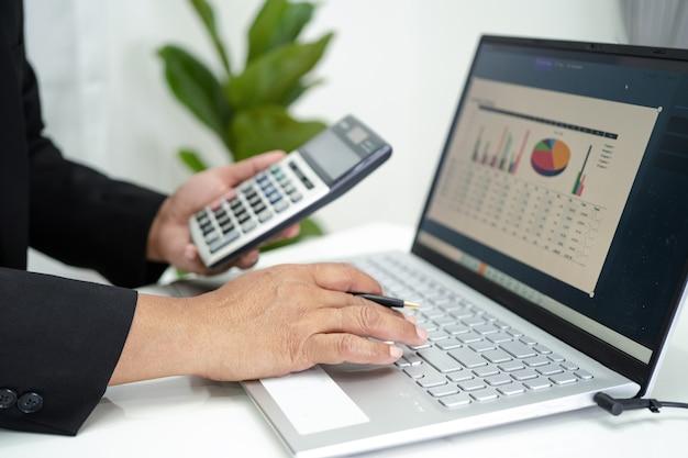 Contador asiático trabalhando relatórios financeiros, projeto de contabilidade com gráfico