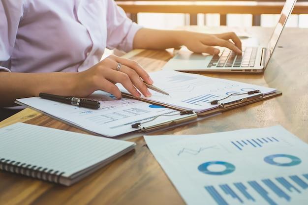 Contador de mulher de negócios trabalhando com relatórios financeiros e computador portátil