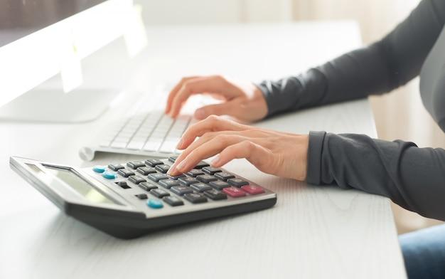 Contador de mulher faz um relatório financeiro em uma calculadora,