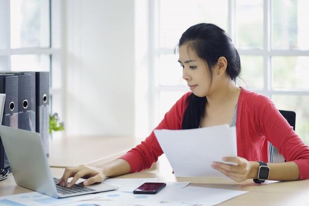 Contador de mulher que trabalha em contas que planejam custo de renda de imposto em análise empresarial