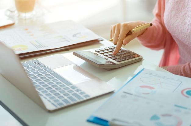 Contador de mulher trabalhando em contas em análise de negócios com gráficos e documento relatório de dados financeiros