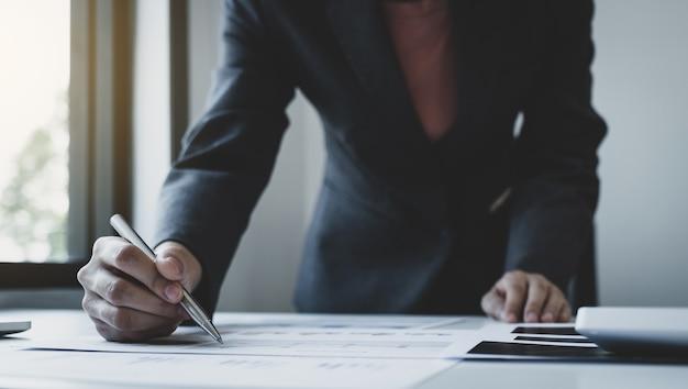 Contador empresária mão segurando uma caneta e usar laptop fazendo conta para pagar impostos na mesa branca no escritório de trabalho.