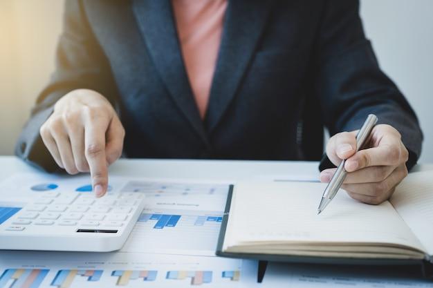 Contador empresária usa notebook e calculadora fazendo conta para pagar impostos na mesa branca no escritório de trabalho.