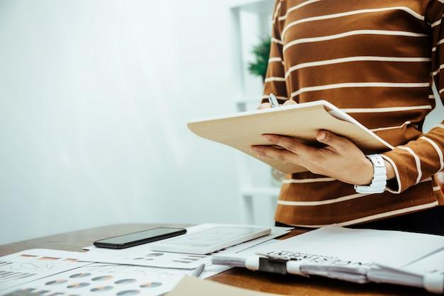 Contador feminino olhando dados financeiros no escritório moderno.