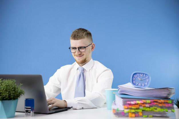 Contador masculino trabalha no escritório, sorrindo, olhando para o sotaque do laptop em azul