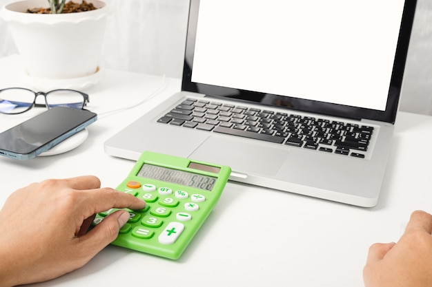 Contador trabalhando e analisando cálculos financeiros com calculadora e laptop