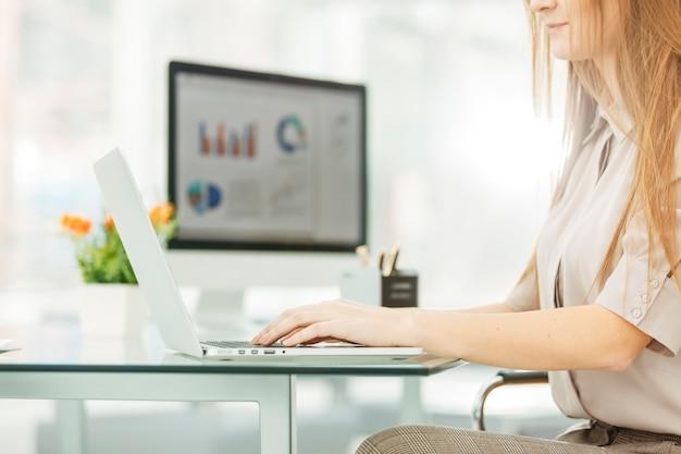 Contador trabalhando em um laptop com gráficos financeiros na área de trabalho