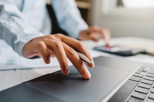 Contador usa calculadora e computador com caneta na mesa no escritório. conceito de finanças e contabilidade