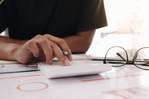 Contador usando uma calculadora para calcular os números. contabilidade, contabilidade do relatório financeiro e ligar para o consultor, conceito de cálculo.