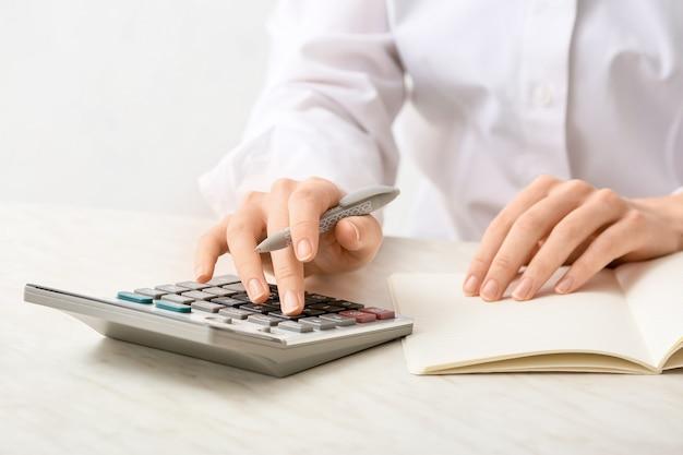 Contadora com calculadora trabalhando no escritório