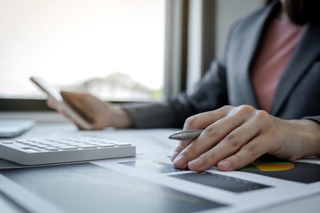 Contadora de mulheres de negócios mão segurando a caneta e usar laptop fazendo conta para pagar impostos na mesa branca no escritório de trabalho.