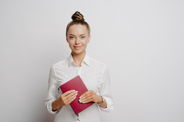 Contadora feminina de camisa branca com cabelo preso, segurando o caderno vermelho que contém os registros e as transações de sua empresa e olhando para a câmera com confiança, isolada em um fundo cinza