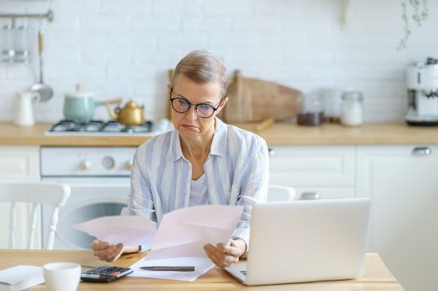 Contadora moderna concentrada de mulher de negócios madura usando óculos, analisando documentos enquanto