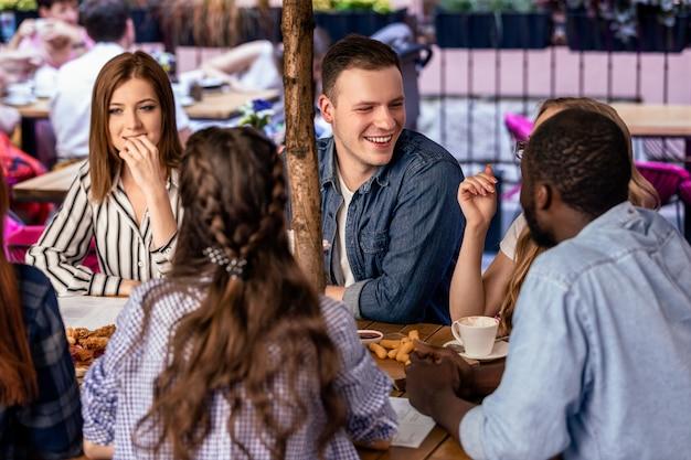 Contando piadas para amigos próximos com uma atmosfera informal no terraço ao ar livre de um café