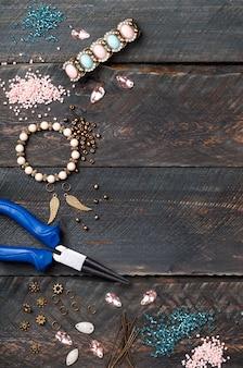 Contas, alicate, corações de vidro e acessórios para criar joias feitas à mão em mesa de madeira