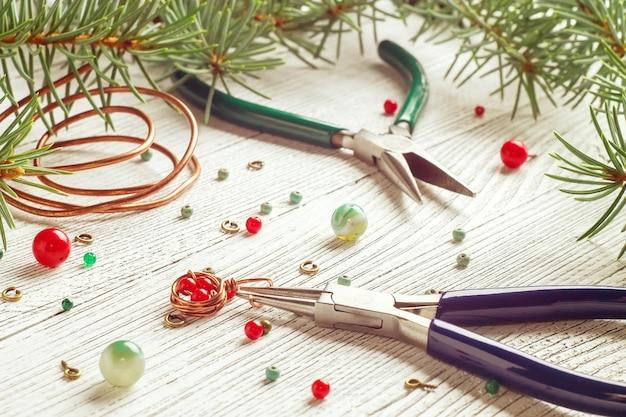 Contas coloridas, fio de cobre e ferramentas de joalheria. fio revestido. espírito de natal