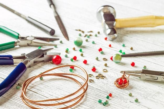 Contas coloridas, fios de cobre e ferramentas de joalheria em uma mesa de luz. fio revestido