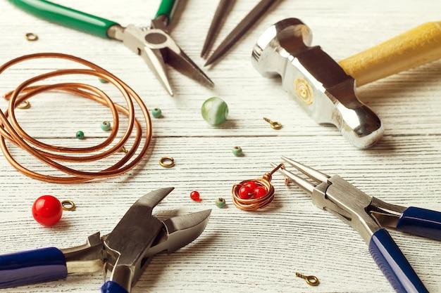 Contas coloridas, fios de cobre e ferramentas de joalheria. fio revestido