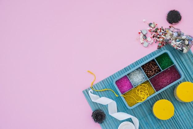 Contas coloridas; fita e miçangas no pano de fundo rosa
