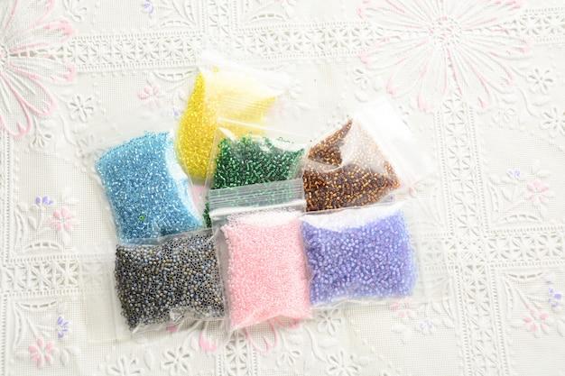 Contas coloridas na superfície de tecido branco, várias formas e cores para fazer jóias