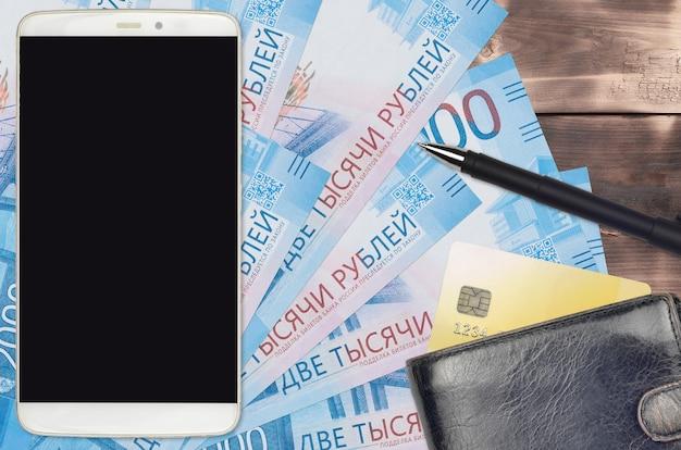 Contas de 2.000 rublos russos e smartphone com bolsa e cartão de crédito. conceito de pagamentos eletrônicos ou comércio eletrônico. compras online e negócios com uso de dispositivos portáteis