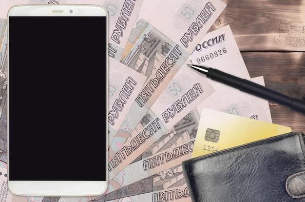 Contas de 50 rublos russos e smartphone com bolsa e cartão de crédito. conceito de pagamentos eletrônicos ou comércio eletrônico. compras online e negócios com uso de dispositivos portáteis