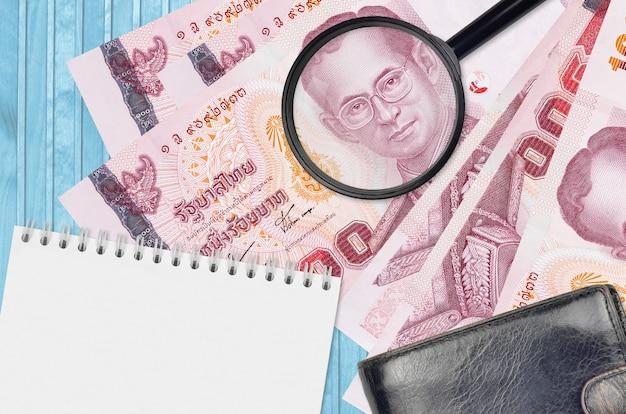 Contas de baht tailandês e lupa com bolsa preta e bloco de notas