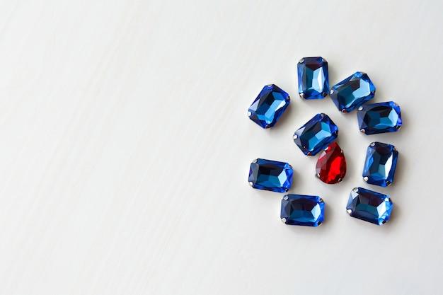 Contas de cristais de pedras azuis e vermelhas de diferentes formas em um fundo branco de madeira