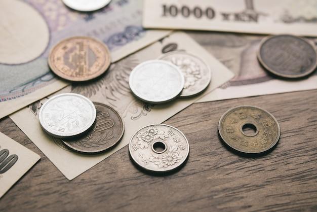 Contas de dinheiro de iene japonês e moedas na mesa de madeira