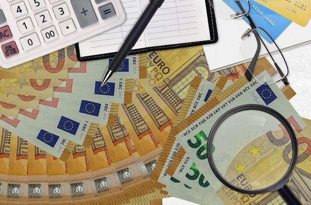 Contas de euro e calculadora com óculos e caneta