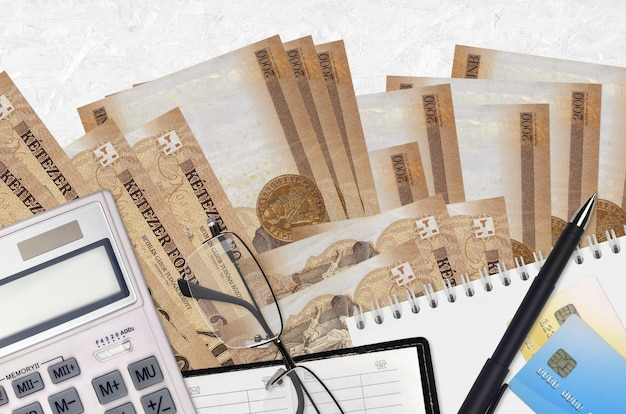 Contas de forinto húngaro de 2000 e calculadora com óculos e caneta