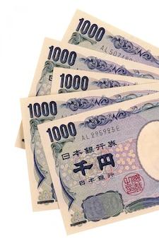 Contas de moeda do japonês 1000 ienes isoladas inteiramente contra o branco (com trajeto).