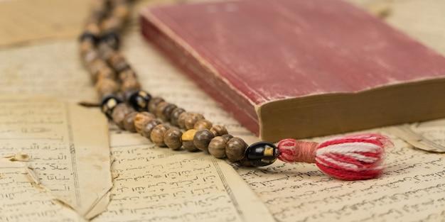 Contas de oração muçulmanas com alcorão e folhas com escritas árabes antigas. conceitos islâmicos e muçulmanos
