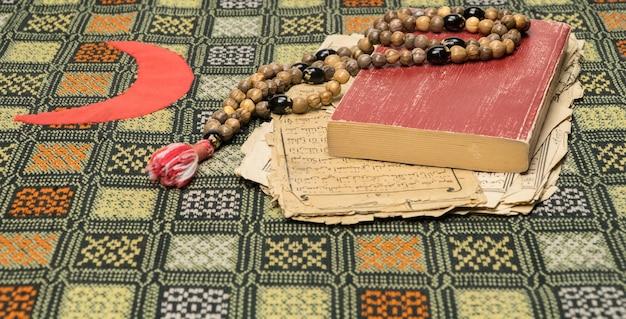Contas de oração muçulmanas com alcorão e folhas com escritas árabes antigas