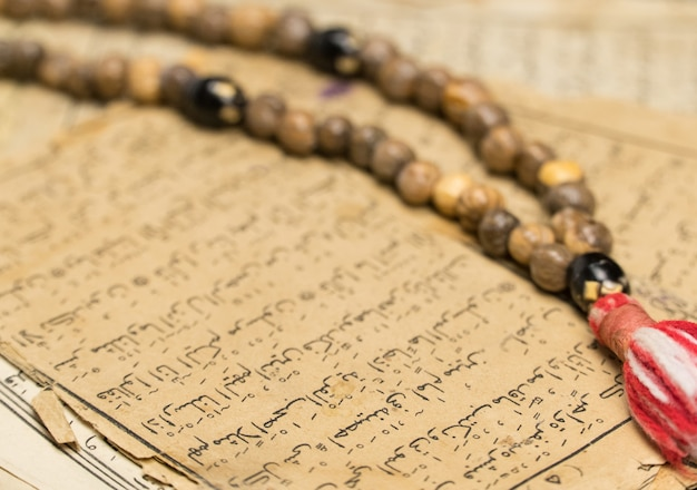 Contas de oração muçulmanas com páginas antigas dos conceitos islâmicos e muçulmanos do alcorão