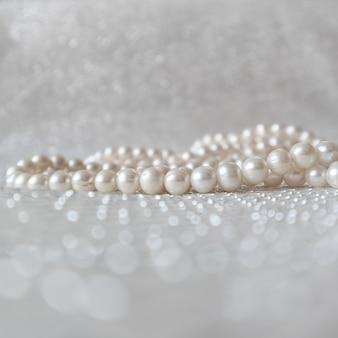 Contas de pérolas brancas naturais em fundo cintilante